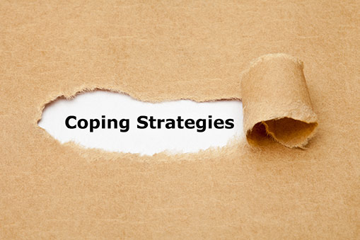 """ripped paper revealing the words """"coping strategies"""""""